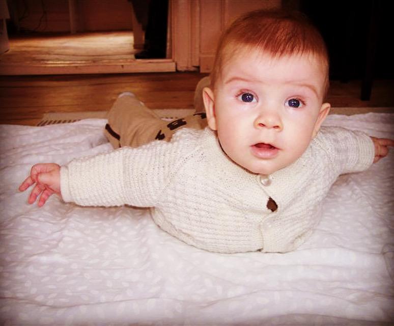 Barn på 5 måneder ligger på maven i flyverstilling